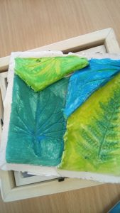 Leaf impressions in clay painted in blue and green colours