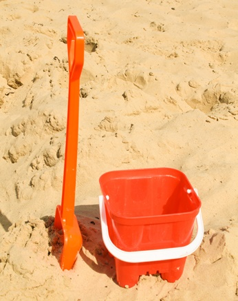 Red plastic bucket and spade in the sand