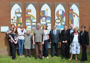 Memory Lane artists and creators in front of the finished five panel mosaic