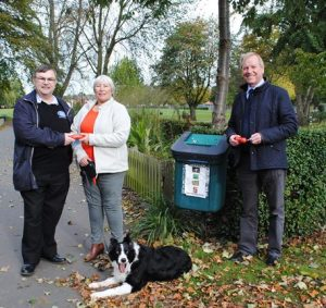 Dog owner Christine is handed a dog bag dispenser from Chair of Boston Big Local